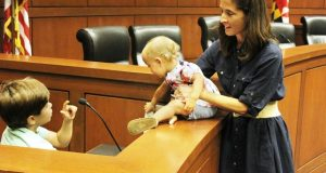 Natalie Carpenter, right, an evening student at University of Maryland Francis King Carey School of Law, stands in the ceremonial moot courtroom with her children Beckett, 7, and Marlowe, 18 months. (The Daily Record / Heather Cobun)