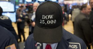 "FILE- In this Jan. 4, 2018, file photo a stock trader wears a ""Dow 25,000"" hat at the New York Stock Exchange. If stocks don't drop significantly by the close of trading Wednesday, Aug. 22, the bull market that began in March 2009 will have lasted nine years, five months and 13 days, a record that few would have predicted when the market struggled to find its footing after a 50 percent plunge during the financial crisis. (AP Photo/Mark Lennihan, File)"