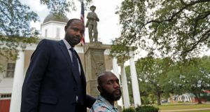 Ronnie Anderson, right, an African-American man charged with possession of a firearm by a convicted felon, poses for a photo with his lawyer Niles Haymer, left, in front of a confederate statue on the lawn of the East Feliciana Parish Courthouse, where he is facing the charge, in Clinton, La. Anderson unsuccessfully asked for his case to be moved to another location because the courthouse where he's being tried has a Confederate monument in front of it. (AP Photo/Gerald Herbert)