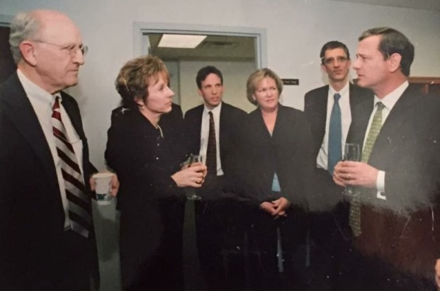 Lyle Denniston, left, holds court with Chief Justice John G. Roberts Jr., right, while Supreme Court staff and press corps members look on in 2005. (Supreme Court photo)