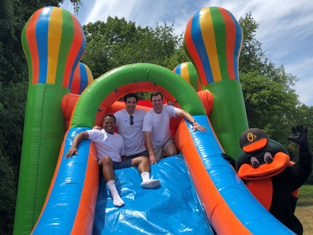 Three DLA Piper summer associates spend some time in one of the two bounce houses at the firm's Horizon Day Camp Carnival at Maryvale Preparatory School in Lutherville. (Photo courtesy of Horizon Day Camp staff)