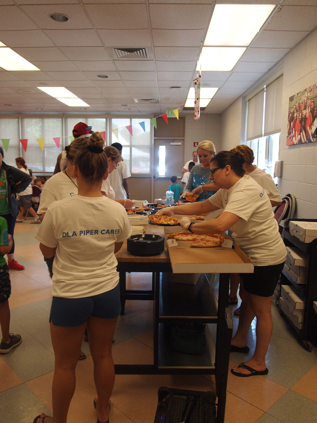 Staff from the Baltimore office of DLA Piper help serve pizza to hungry campers during the firm's Horizon Day Camp Carnival. (Photo courtesy of Horizon Day Camp staff)