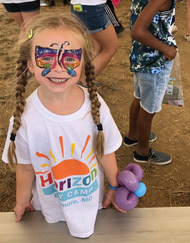 A young camper enjoyed participating in balloon art and face-painting at the second annual Horizon Day Camp carnival hosted by DLA Piper. (Photo courtesy of Horizon Day Camp staff)