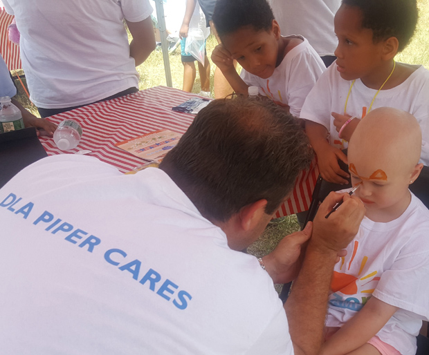 DLA Piper partner Tom Pilkerton leads the face-painting booth at the firm's second annual Horizon Day Camp Carnival. (Photo courtesy of Horizon Day Camp staff)
