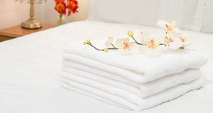 Freshly laundered white fluffy towels in bedroom interior (springfield / Depositphotos.com)
