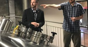 Union Craft Brewing co-founder and owner Adam Benesch leads state officials on a tour of the new Union Collective brewery.