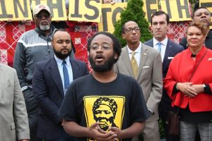Terrell Askew, a member of the Remington Housing Workgroup, speaks during a rally outside City Hall on Thursday. Backers of a proposal showed support for the Fund the Trust Act prior to the bill's first hearing. (Adam Bednar)