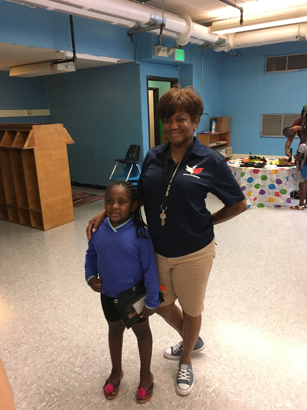 Kindergarten student Paige Smith stands with Heidi Stevens, community school coordinator with James McHenry Elementary School, during the celebration of the school's newly renovated classroom. (Photo by Annie Yeager, Maryland Proton Treatment Center)