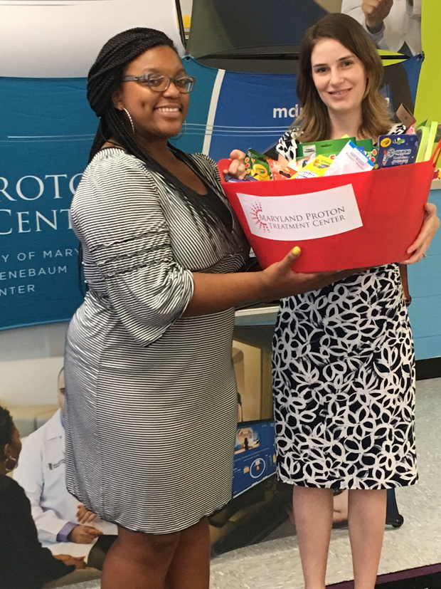 Brittany Skinner, left, a kindergarten teacher at James McHenry Elementary School, accepts school supplies from Allison Shafer, the marketing manager with Maryland Proton Treatment Center as it helped the school celebrate the renovation of its kindergarten classroom. (Photo by Annie Yeager, Maryland Proton Treatment Center)