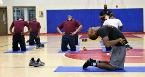 Larry Jackson leads boys at the Baltimore City Juvenile Justice Center in a yoga pose last month. The center started offering yoga classes last year. (Courtesy of Eric Solomon)