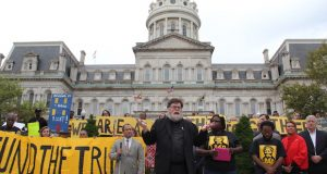 "Father Ty Hullinger prays in front of City Hall in September with supporters of the ""Fund the Trust Act.""  (Adam Bednar)"