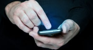 Man in black shirt is typing a text message on his smartphone, close up image, focus on hands and the phone device.