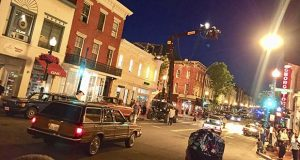 This image provided by Erin Aulov shows a scene on Wisconsin Avenue in the Georgetown section of Washington on July 1, 2018, during the filming of the new Wonder Woman movie. When the Wonder Woman sequel filmed in several locations around Washington this summer, it was a genuine novelty. In any given year, there are usually multiple movies and TV shows set in Washington, but very few actually do the bulk of their filming here.  (Erin Aulov via AP)