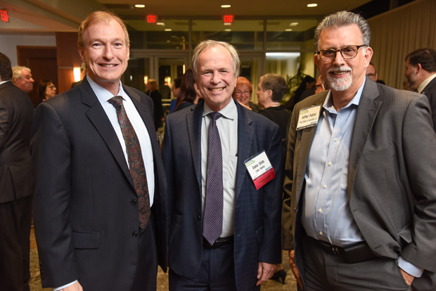 From left, Mark Hegarty, vice president of business development with reception sponsor Melwood; 2018 Most Admired CEO winner Dana Stein, the executive director of Civic Works; and Arthur Putzel, a principal with Trout Daniel & Associates LLC, pause during the networking reception for a photo. (Photo by Maximilian Franz)
