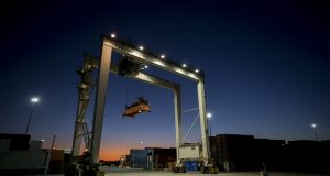 FILE- In this Jan. 30, 2018, file photo a rubber tire gantry moves into position to transfer shipping containers at the Georgia Ports Authority's Port of Savannah in Savannah, Ga. On Wednesday, Nov. 28, the Commerce Department issues the final estimate of how the U.S. economy performed in the July-September quarter. (AP Photo/Stephen B. Morton, File)