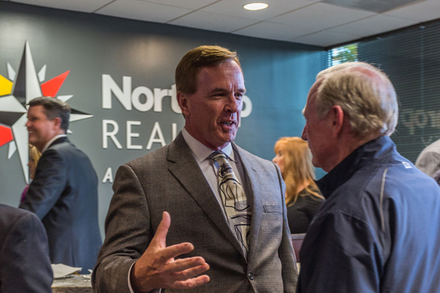 Mark Kleinschmidt, President and CEO of the Anne Arundel County Chamber of Commerce, engages in a conversation with a guest at the grand opening celebration of Northrop Realty's new office location in Annapolis. (Photo courtesy of Northrop Realty)