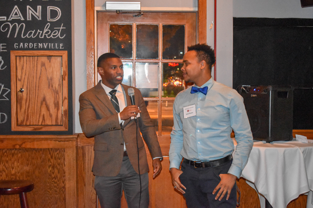 Darryl Tarver, left, an associate in the litigation practice at DLA Piper and chair of the leadership group for The Equal Justice Associates, hands over the microphone to Jamar Barnes to speak to the audience at the Pratt Street Ale House in Baltimore during a launch party for the group. (Photo by Bill Hall, MSBA)