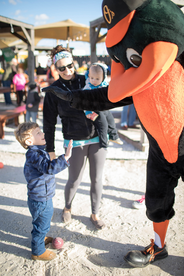 Chidren lined up to give a high-five to The Oriole Bird at the fourth annual Stars, Stripes & Chow chili cookoff , which was presented by the Baltimore Orioles. (Photo courtesy of The Baltimore Station)