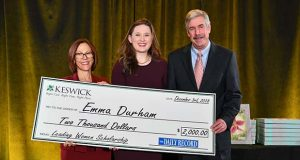 Emma Durham stands holds a ceremonial check commemorating her scholarship win, flanked by Carmel Roques, CEO of Keswick, left, and Tom Baden Jr., editor of The Daily Record. (Maximilian Franz / Special to The Daily Record)