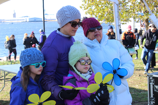 During the Flower Garden Ceremony, Robin Decker, center, holds a yellow flower to acknowledge her role as a caregiver to her mother Maria Borrero, right, who has Alzheimer's disease, and was joined by her 7-year-old twin daughters. Borrero served as executive director of the Equal Opportunity Commission in the Clinton administration.  (Photo by Renee Johnson)
