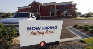 FILE- This July 25, 2018, file photo shows a help wanted sign at a new Zaxby's restaurant in Madison, Miss. On Monday, Dec. 10, the Labor Department reports on job openings and labor turnover for October. (AP Photo/Rogelio V. Solis, File)