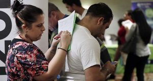 FILE - In this Jan. 30, 2018, file photo, Loredana Gonzalez, of Doral, Fla., fills out a job application at a JobNewsUSA job fair in Miami Lakes, Fla. 2019 should be another banner year for workers, says Mark Zandi, chief economist at Moody's Analytics. (AP Photo/Lynne Sladky, File)