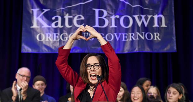 In this Nov. 6, 2018 file photo, Gov. Kate Brown makes a heart-shape with her hands as she addresses the crowd after winning re-election to her first full term in Portland, Ore. When Oregon's next labor commissioner was sworn in on Monday, Jan. 7, 2019, for the first time in Oregon history a majority of statewide elected executive offices will be held by women. Gov. Kate Brown and Attorney General Ellen Rosenblum will administer the oath of office to Val Hoyle. (AP Photo/Steve Dykes, File)