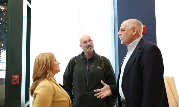 From left, Stephanie Nay, graphic design manager with Harford County Government; Matt Button, photo editor of The Aegis newspaper; and Bob Bloom, general manager of WXCY-FM 103.7, engage in a conversation during the State of the County luncheon. (Photo by Kate Rodriguez)