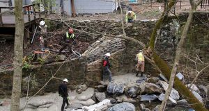 A crew works to repair a retaining wall in Old Ellicott City along a creek in the Tiber River watershed. The town suffered two deadly floods, causing millions of dollars in damage, since the summer of 2016. (Adam Bednar)