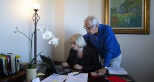 In this Feb. 6, 2019, photo Debbie Douglas works on her computer as her husband and business partner, Gary, watches in their home office in Newport Beach, Calif. In business together for 16 years, the Douglases have found that being co-owners of a public relations firm requires them to be more direct with each other than they once were as spouses. (AP Photo/Jae C. Hong)
