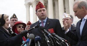 The National Judge Advocate for The American Legion Kevin Bartlett, center, speaks at a news conference following oral arguments on the fate of a cross-shaped war memorial on Wednesday, Feb. 27, 2019 at the Supreme Court in Washington. (AP Photo/Kevin Wolf)