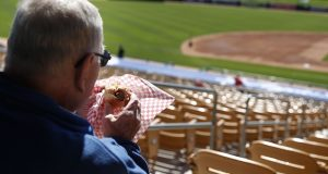 FILE - In this March 4, 2015 file photo, a fan eats a hot dog before a spring training exhibition baseball game between the Chicago White Sox and the Los Angeles Dodgers, in Phoenix. Owners who take customers to sporting events or the theater or treat them to a round of golf will have to foot the entire bill for those activities. The new tax law has done away with the entertainment deduction for businesses. (AP Photo/John Locher, File)