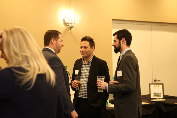 Alex Penduck, center, an insurance adviser with WSMT Insurance; and colleague Ryan Hayes, right, an account executive with the firm, engage in a conversation. (Photo by Kate Rodriguez)