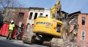 Demolition crews demolish blighted housing to make way for new homes in the Druid Hill area. (Adam Bednar)