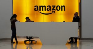 People stand in the lobby of Amazon offices in New York. (AP Photo/Mark Lennihan, File)