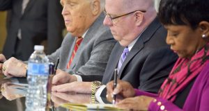 Gov. Larry Hogan signs legislation providing unemployment benefits to Maryland federal workers in the event of a government shutdown. At left is Senate President Thomas V. Mike Miller Jr., and on right is House Speaker Pro Tem Del. Adrienne Jones, D-Baltimore County. (Bryan P. Sears)
