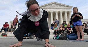 Alice Wisbiski, dressed as Supreme Court Associate Justice Ruth Bader Ginsburg, is joined by others as a group do exercises on the steps of the Supreme Court in Washington, Friday, March 15, 2019, to celebrate Ginsburg's upcoming birthday 86th birthday. (AP Photo/Susan Walsh)