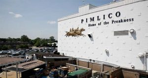 """FILE - In this May 15, 2018 file photo, people walk outside of a building at Pimlico Race Course as preparations take place for the Preakness Stakes horse race, in Baltimore. Baltimore has ratcheted up a bitter dispute with the owners of the historic racetrack in an effort to seize a nearly 150-year-old course and block the move of one of America's premier horse races out of the city where it was first run in 1873. Under state law, the Preakness Stakes - the middle jewel of the Triple Crown of thoroughbred horse racing - can be moved to another track in Maryland """"only as a result of a disaster or emergency."""" But the Canada-based development company that owns and operates the rundown Pimlico Race Course has made it abundantly clear that it wants to move the storied race out of the city. (AP Photo/Patrick Semansky, File)"""