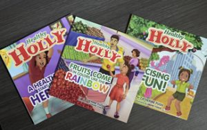 """This March 2019 photo taken in Baltimore, shows copies of Baltimore Mayor Catherine Pugh's self-published """"Healthy Holly"""" illustrated paperbacks for children. Baltimore's embattled mayor announced Monday, April 1 that she is taking an indefinite leave of absence, just as a political scandal intensifies over what critics call a """"self-dealing"""" book-sales arrangement that threatens her political career. The various officials' calls came shortly after Kaiser Permanente disclosed that it paid $114,000, between 2015 and 2018, for roughly 20,000 copies of Pugh's children's books. And it came about two weeks after news broke that since 2011, Pugh has received $500,000 selling her books to the University of Maryland Medical System, a $4 billion hospital network that's one of the largest private employers in the state. (Jerry Jackson/The Baltimore Sun via AP)"""