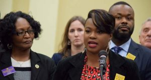 Ricarra Jones of 1199 SEIU (In red at the mic) with Del. Diana Fennell, D-prince George's County (left) and Sen. Cory McCray, D-Baltimore City (on right over Jones's Shoulder) in January 2019. Fennell and McCray are the House and Senate lead sponsors of the minimum wage bill.