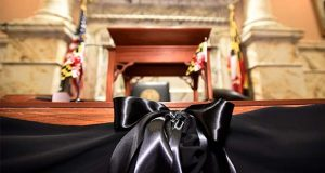A black bow trims the speaker's rostrum in the Maryland House of Delegates chamber in Annapolis, Md., Monday, April 8, 2019, the final day of the state's 2019 legislative session. Michael Busch, the longest-serving Maryland House speaker, died Sunday, April 7. (AP Photo/Steve Ruark)