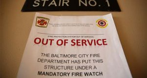 In this Feb. 22, 2019 photo, a sign alerts residents in Rosemont Tower in Baltimore that the fire sprinkler system is out of service, requiring a firefighter to stand watch around the clock. Largely due to complexes such as Rosemont Tower, since 2013 Maryland had the country's highest inspection failure rate for public housing at 32%. (AP Photo/Patrick Semansky)