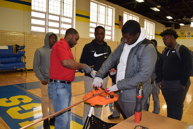 One of the students from Mergenthaler Vocational-Technical High School gets some hands-on experience with surveying equipment during the presentation. (Photo courtesy of Urban Alliance)