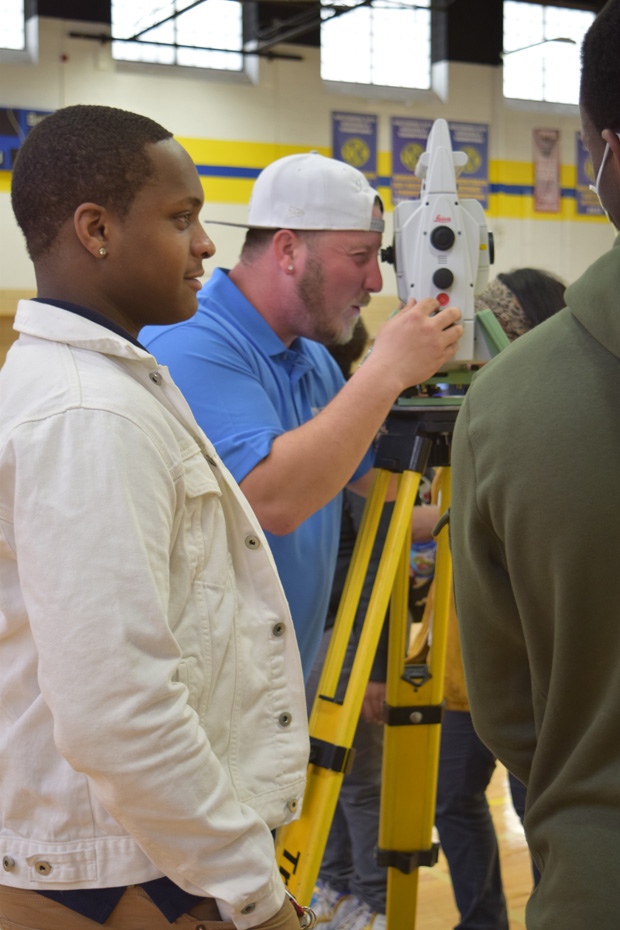 Joshua Hood of Century Engineering demonstrates a piece of surveying equipment to teach students about geographic information system mapping. (Photo courtesy of Urban Alliance)