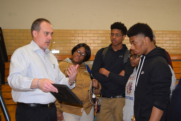 TJ Frazier of Precision Measurements Inc. displays some information to students to introduce Baltimore teens to career pathways in the growing land surveying industry. (Photo courtesy of Urban Alliance)