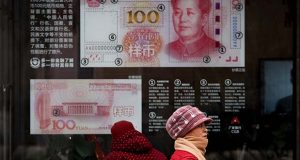 FILE - In a Monday, Feb. 18, 2019 file photo, women walk by a bank window panel displaying the security markers on the latest 100 Yuan notes in Beijing. The Trump administration has again decided not to label China or any other country as a currency manipulator. But in a report to Congress, the administration is keeping China on a list of countries whose trade surpluses with the United States and other indicators are closely tracked.  (AP Photo/Andy Wong, File)