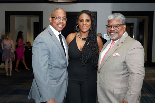 From left, Damion Cooper, founder and executive director of Project Pneuma; Chanel Rhoads-Reed, external affairs manager wih BGE; and Robert Matthews, director of human resources with BGE, take tie for a photo at the Renaissance Baltimore Harborplace Hotel. (Photo by Tracey Brown)