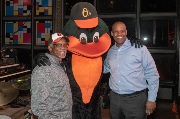 "Linwood Nelson, right, deputy program director at ASRC Federal Research and Technology Solutions, gets a photo with two Baltimore Orioles ""legends,"" outfielder Al Bumbry and The Oriole Bird. (Photo by Colin Stevens)"