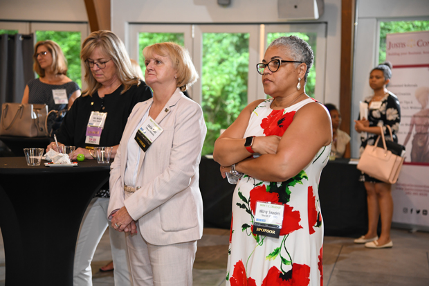 From left, Top 100 Women and Towson University colleagues Deb Moriarty, vice president of student affairs; Louise Miller, AVP for university promotions and events; and Hilary Saunders, director of major gifts, listen to a presentation. (Photo by Maximilian Franz)