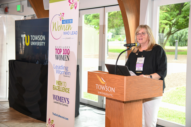 Top 100 Women honorees and co-host Deb Moriarty, vice president of student affairs with Towson University, delivers remarks at The Daily Record's Path to Excellence networking event. (Photo by Maximilian Franz)